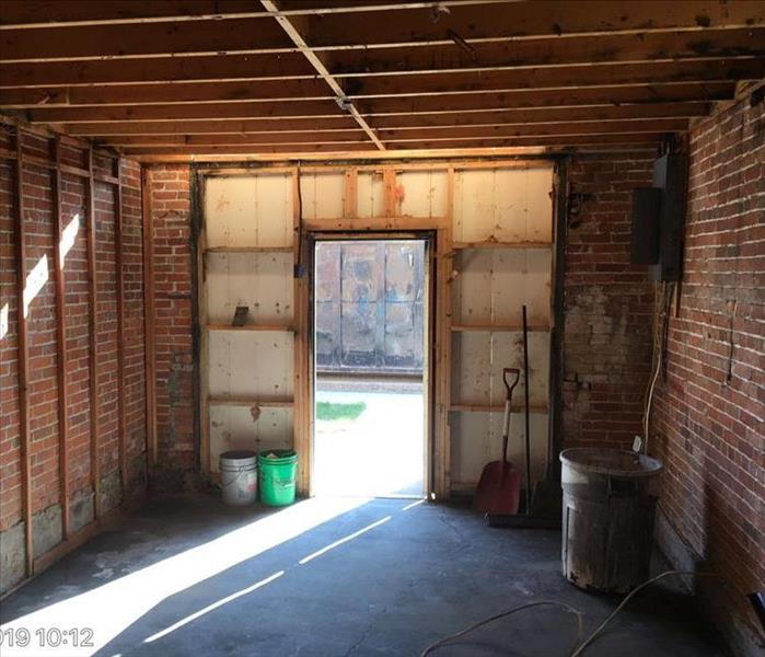 Small side room with stud framing showing and brick behind. Smoke damage throughout whole room